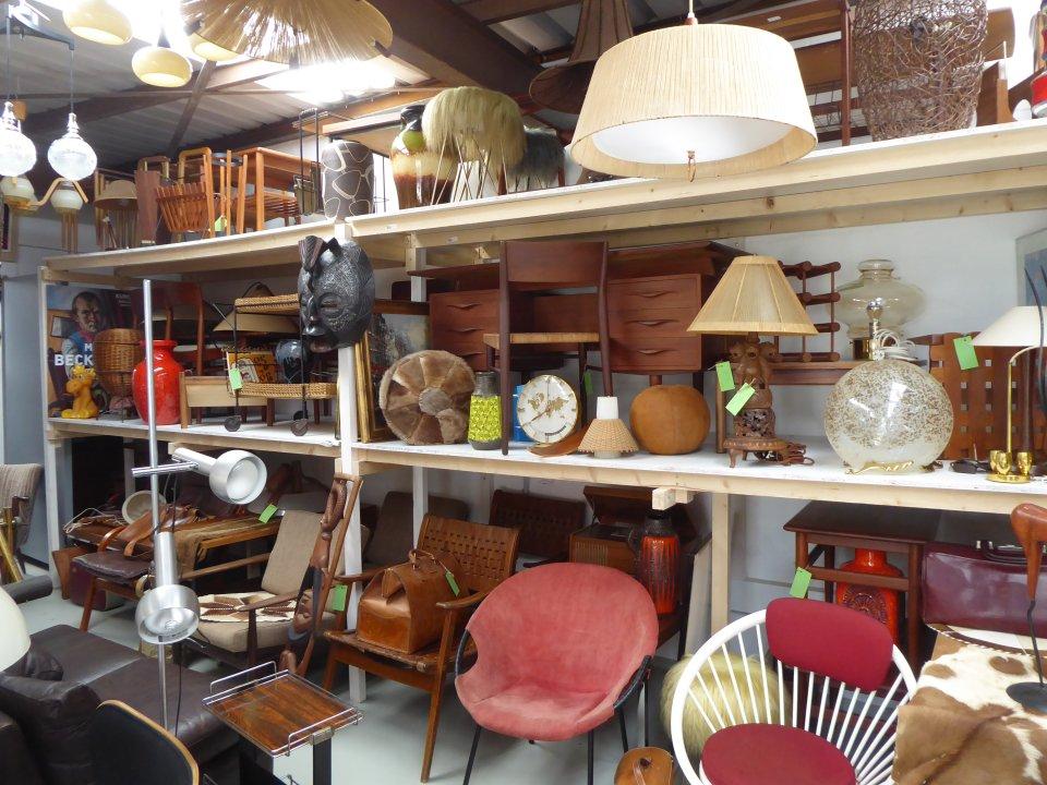 Vintage Möbel werden in einem Lager mit vielen Regalen gelagert.