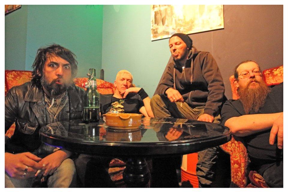 4 Männer mit Bart sitzen auf Sofas und rauchen. Auf dem Tisch steht eine Bierflasche.