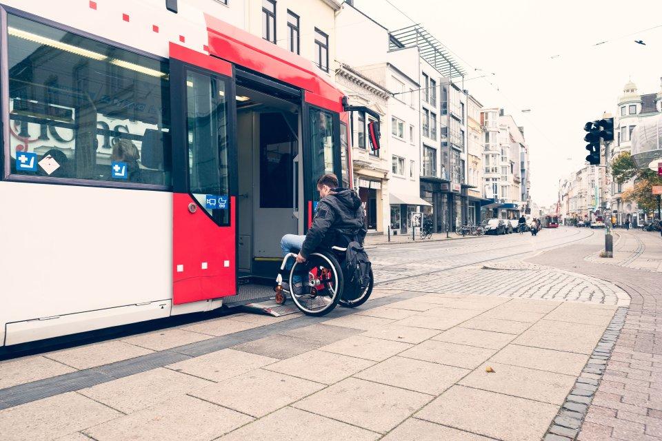 Ein Mann im Rollstuhl fährt auf die Rampe einer Straßenbahn.