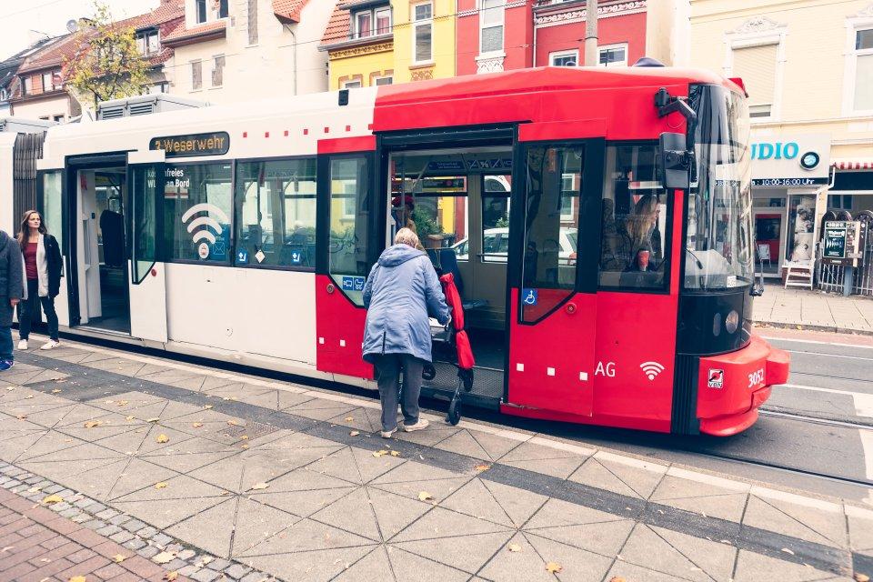 Eine ältere Dame mit Rollator betritt eine Straßenbahn.
