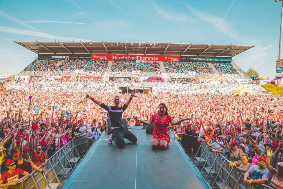 Ein Mann und eine Frau knien auf einer Bühne. Das Publikum hebt die Arme.