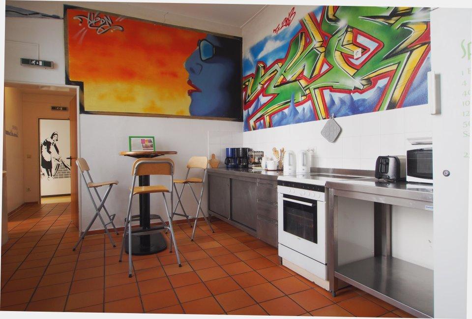 Einfach ausgestattete Küche mit bunten Bildern an der Wand