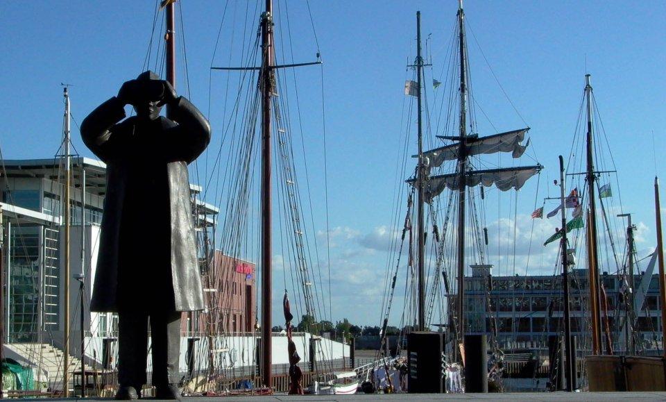 Statue zeigt Mann mit Ferngals am Rande eines Hafenbeckens mit Segelbooten.