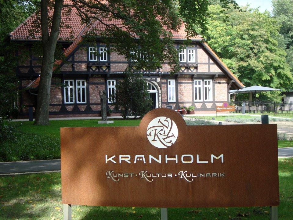 Im Vordergrund ein Schild mit Aufschrift Kränholm, im Hintergrund ein rot geklinkertes Fachwerkshaus