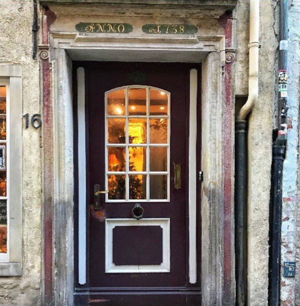 """Eine braune Tür mit Fenster im Schnoor. Links neben der Tür steht die Zahl """"16"""". Über der Tür steht """"ANNO 1738"""""""