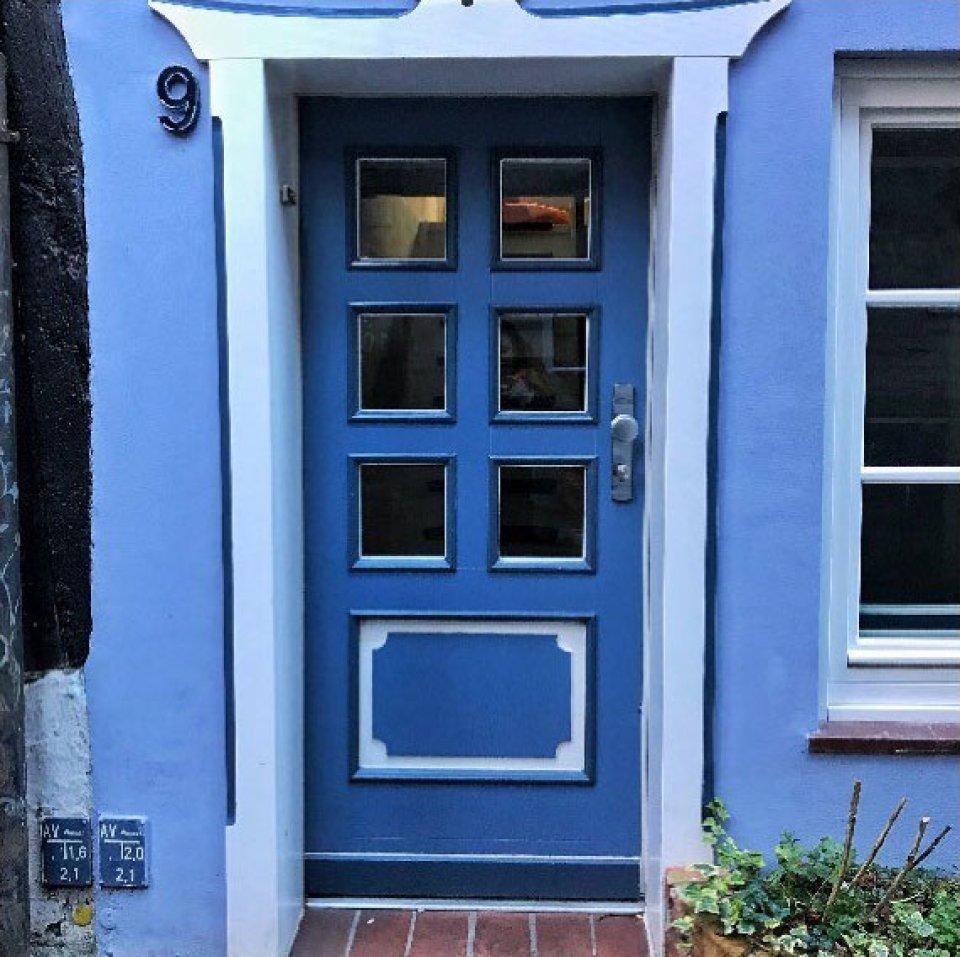 """Eine blaue Tür mit sechs kleinen Fenstern. Links neben der Tür steht die Zahl """"9""""."""