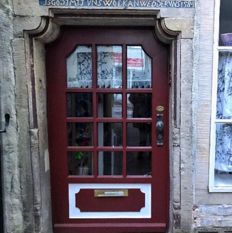 Eine dunkelrote Tür mit zwölf kleinen Fenstern,