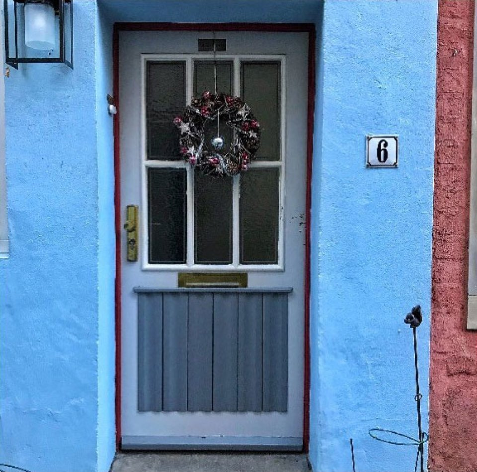 """Eine hellblaue Tür mit sechs kleinen Fenstern. Rechts neben der Tür steht die Zahl """"6"""". An der Tür hängt ein kleiner Weihnachtskranz."""