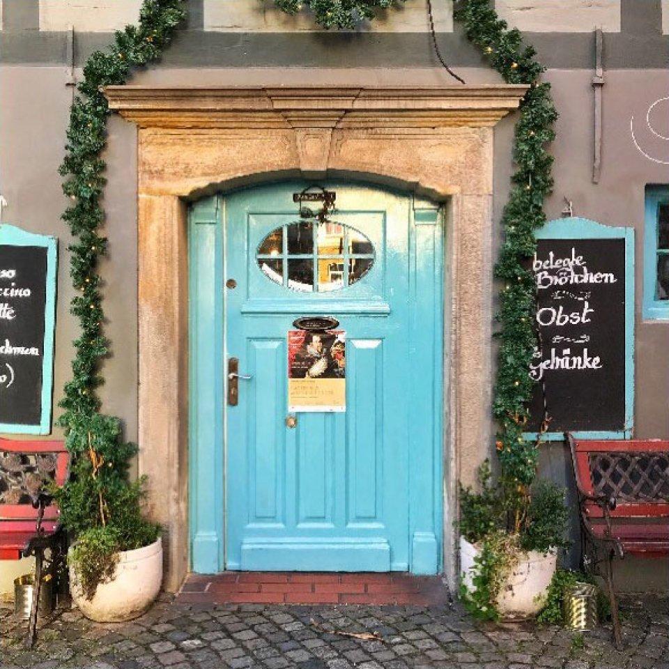 Eine türkise Haustür mit einem runden Fenster. Links und rechts neben der Tür steht jeweils ein Blumentopf mit einer grünen Rankenpflanze, die um den Türrahmen herum verläuft.