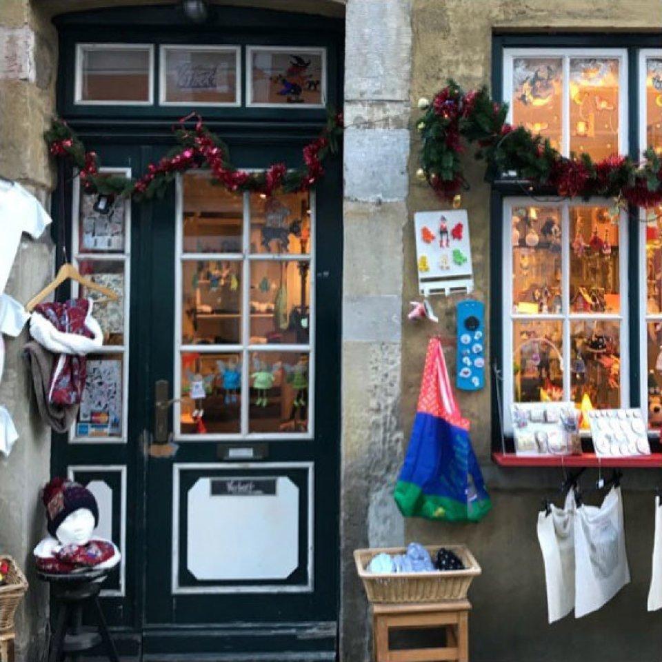 Eine Hausfassade mit einer grünen Tür, die zwölf kleine Fenster hat. An der Fassade ist Weihnachtsdekoration angebracht und vor der Tür steht verschiedene Ware aus.