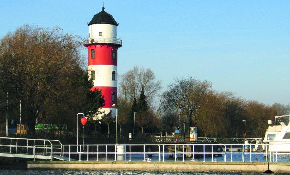 Ein rot-weiß gestreifter Leuchturm, davor ein Steg ins Wasser