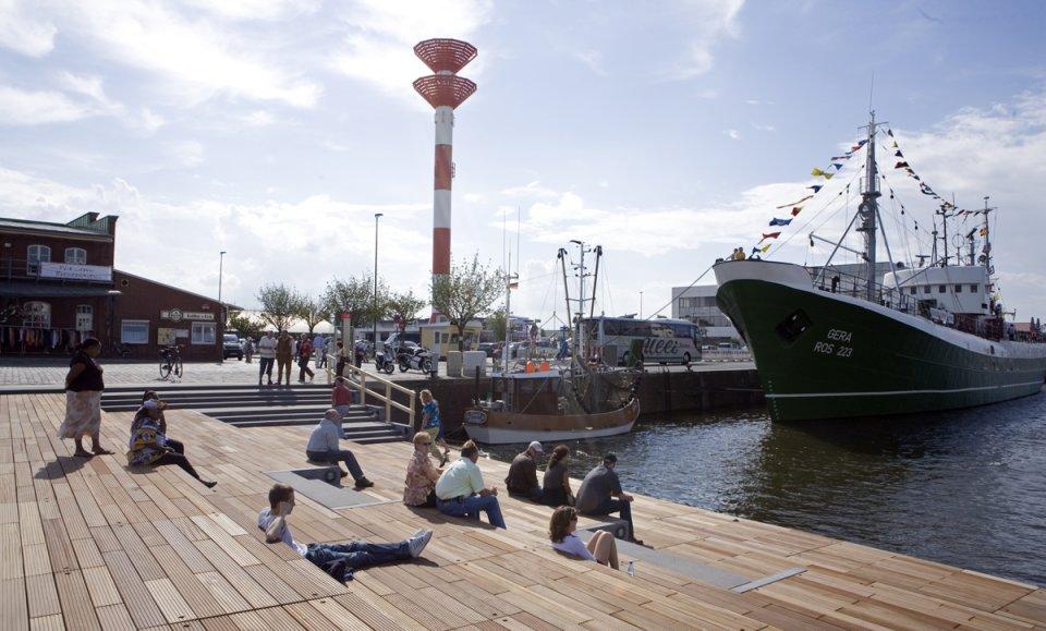 Menschen sitzen in der Sonne auf Holzstufen am Schaufenster Fischereihafen