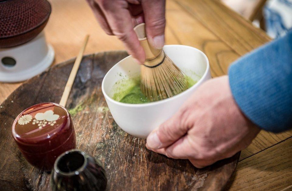 Eine Nahaufnahme der Zubereitung von Matcha-Tee: Eine Besen rührt gerade das grüne Pulver an.