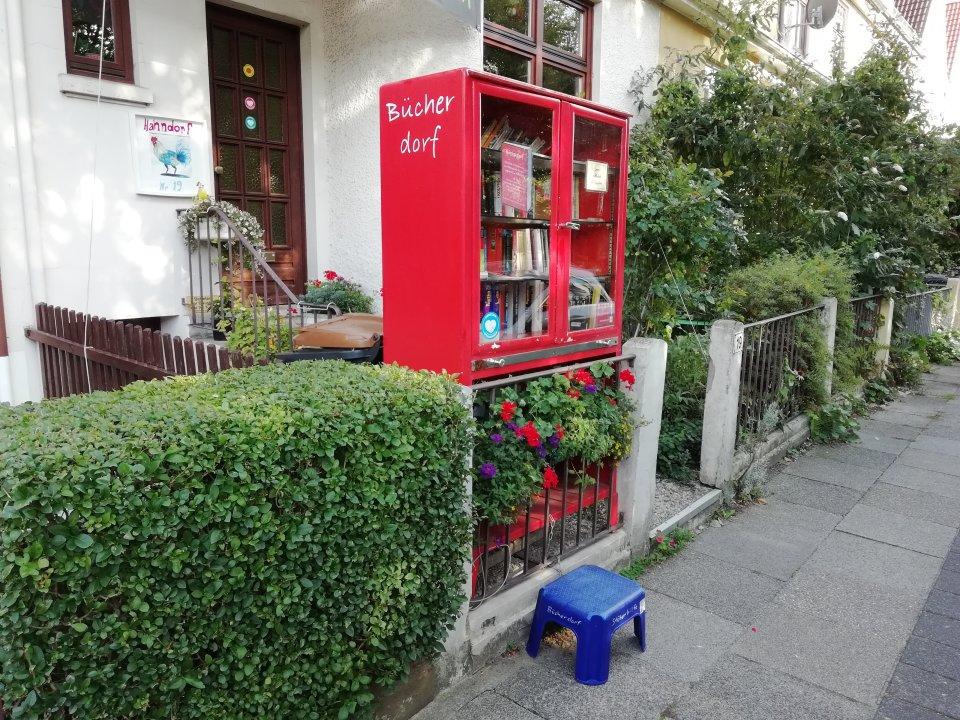 """Ein roter Bücherschrank aus Metall mit der Aufschrift """"Bücherdorf"""" steht in einem Vorgarten vor einem Wohnhaus."""