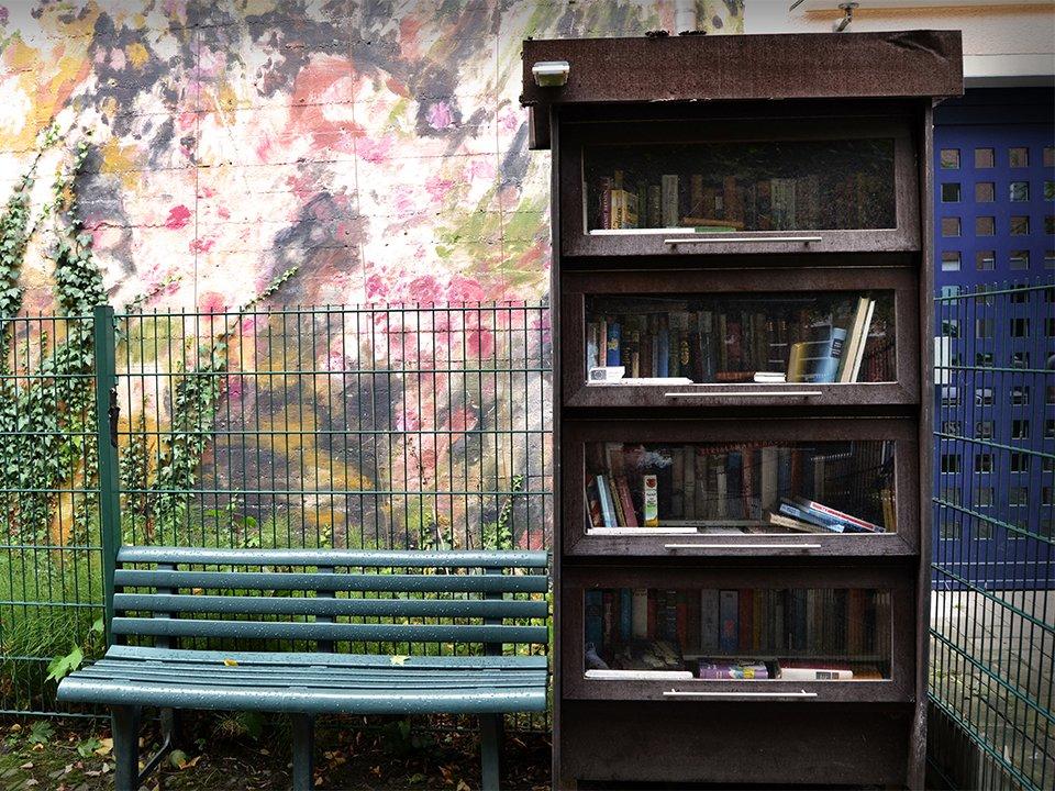 Ein freier Bücherschrank neben einer grünen Parkbank.