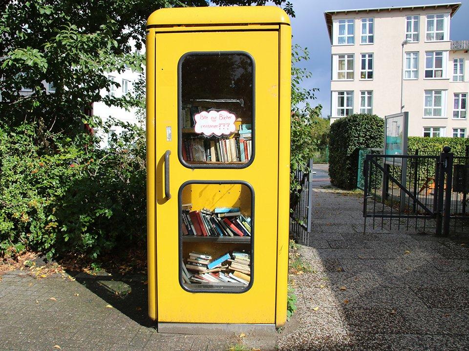 Eine alte, gelbe Telefonzelle wird als öffentlicher Bücherschrank genutzt.