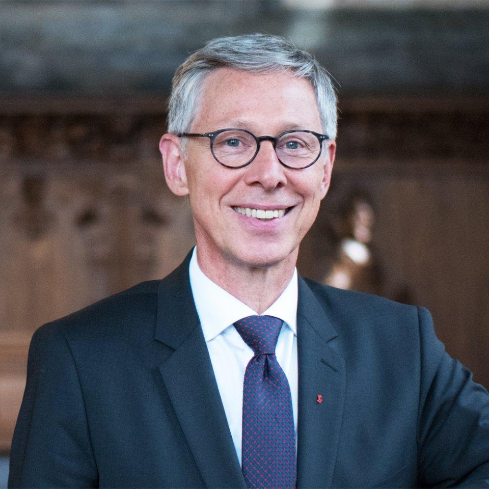 Ein Mann mit runder Brille und Krawatte lächelt in die Kamera