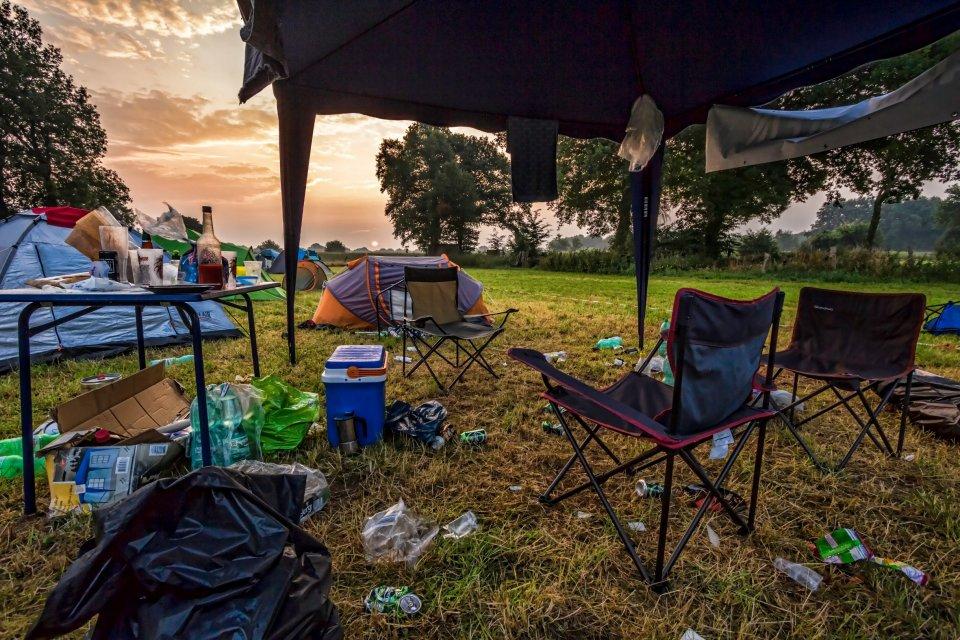 Campingstühle und ein Pavillon stehen zwischen Zelten.