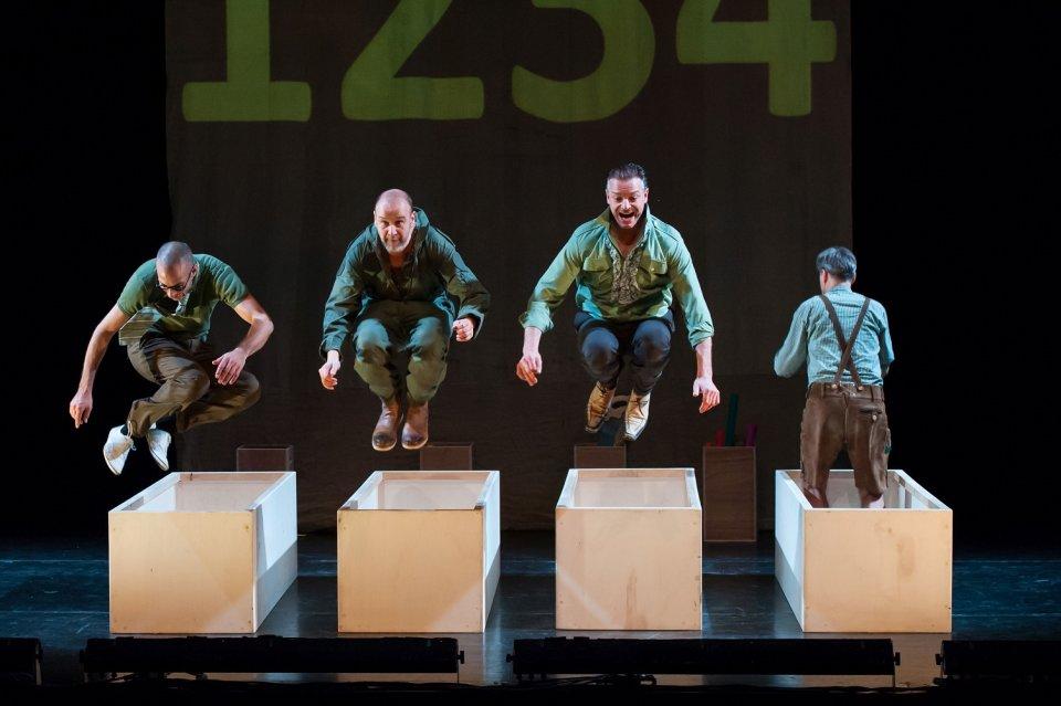 Drei Musiker springen über eine Mox auf der Bühne