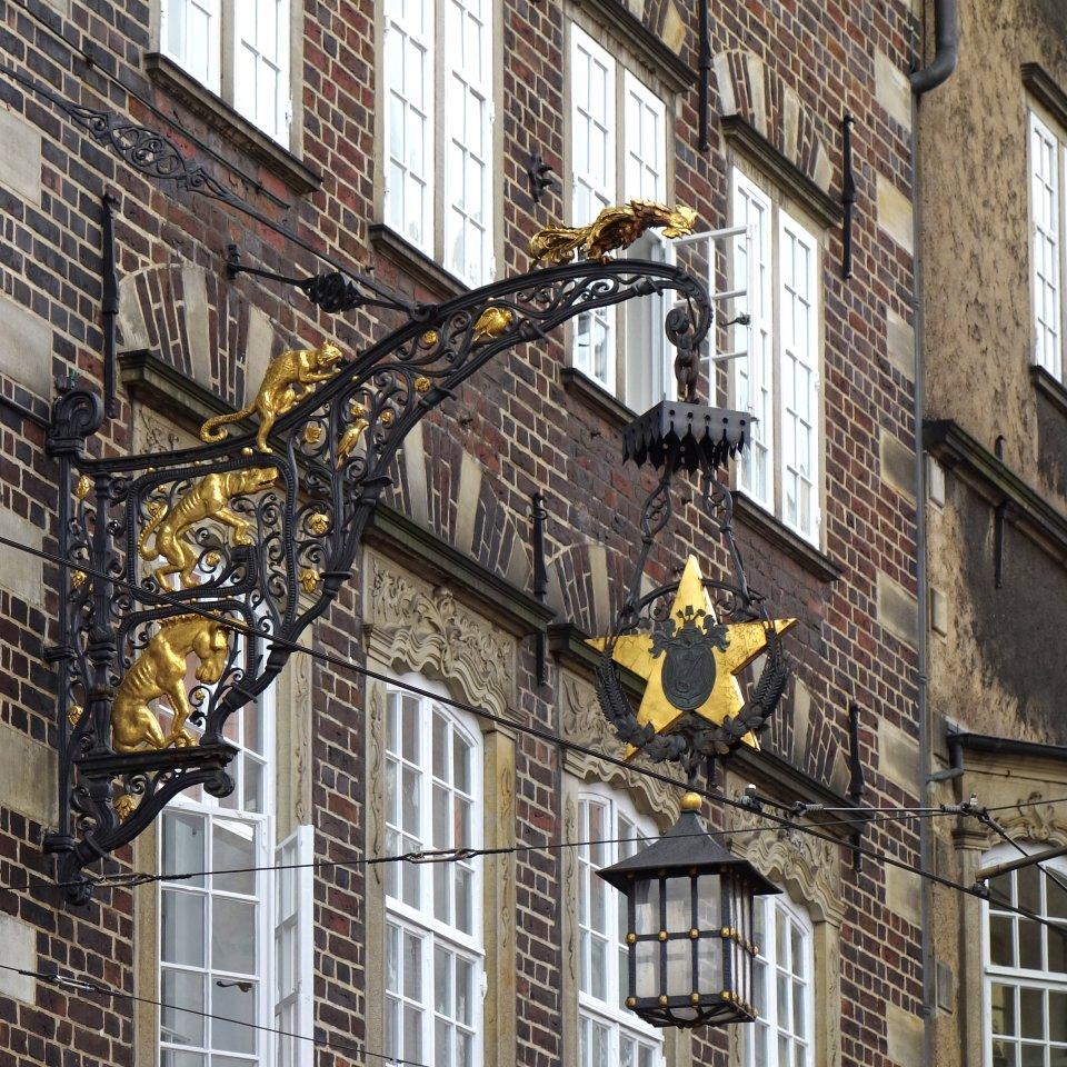 Erschöpft aussehende Figuren der Bremer Stadtmusikanten an einem alten Wirtshausschild