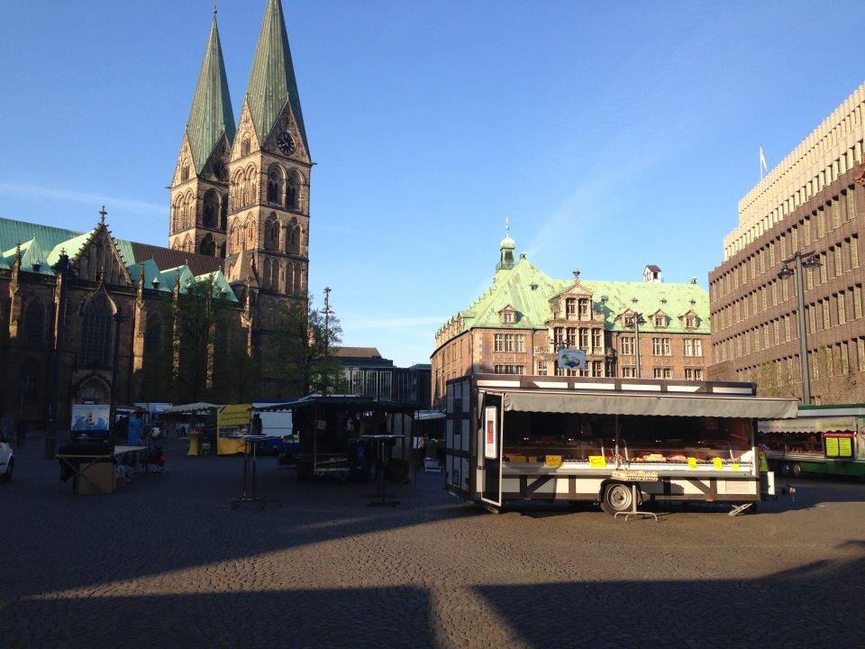 Ein Blick über den Wochenmarkt am Domshof. Im Hintergrund sieht man die grünen Domspitzen.