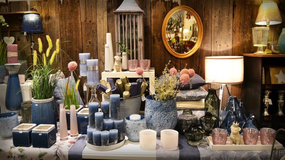 Blaue Dekorationsartikel in Form von Vasen und Kerzen.