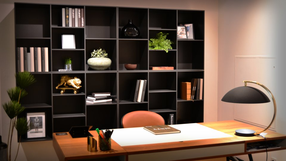 Ein Schreibtisch vor einem schwarzen Regal mit Dekoration.