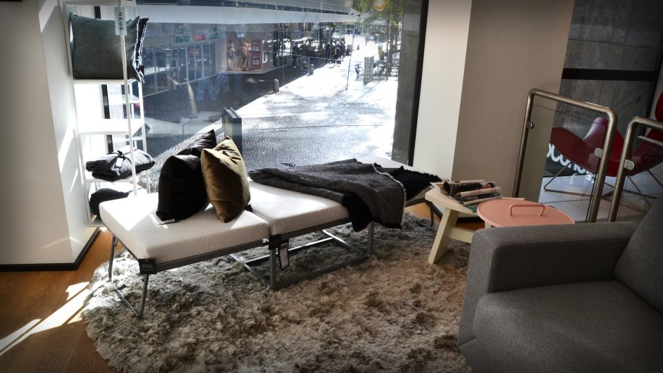 Eine Sitzfläche mit Kissen, einer Decke und Beistelltisch vor einem Schaufenster.