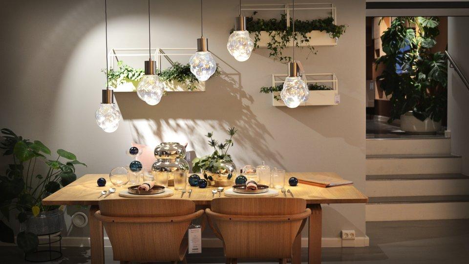 Ein dekorierter Esstisch unter fünf Lampen in Bolia.
