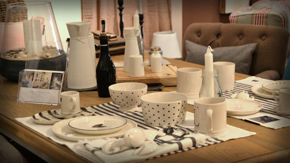 Ein bedeckter Esstisch mit schwarz-weißem Geschirr.