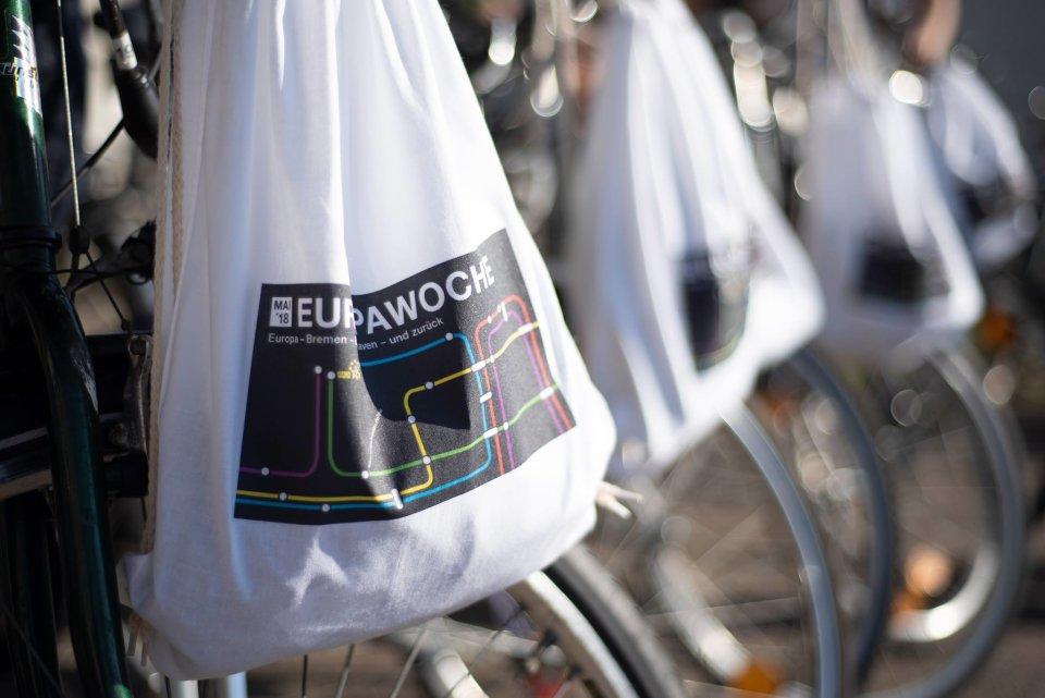 Weiße Stoffbeutel hängen an Fahrradlenkern