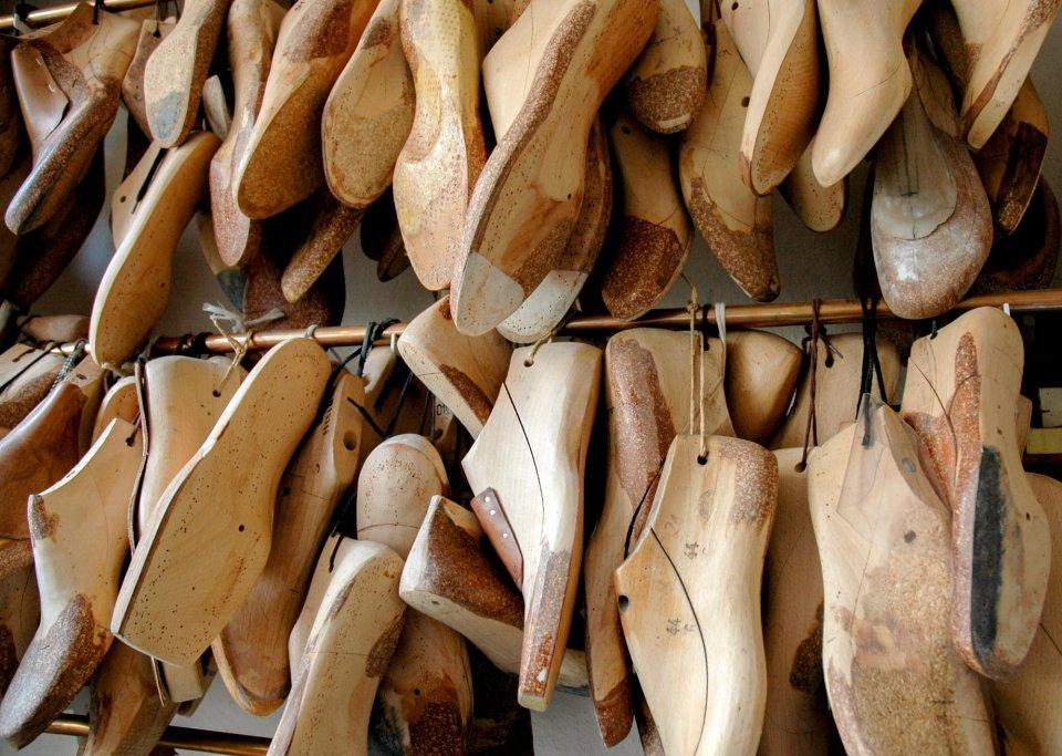 Jede Menge Holzschuhmodelle hängen nebeneinander.