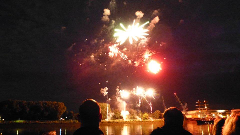 Menschen schauen sich ein Feuerwerk an der Weser an.