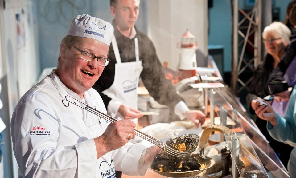 Ein Koch bereitet bei der Fisch & Feines Muscheln zu, während Besucher ihm dabei zusehen.