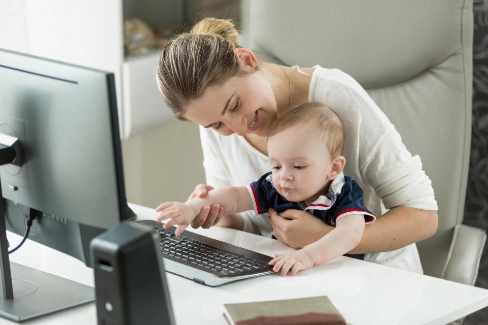 Eine lächelnde Frau sitzt mit einem Kleinkind am Computer.