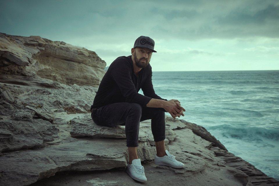 Der Sänger sitzt auf einem Felsen.