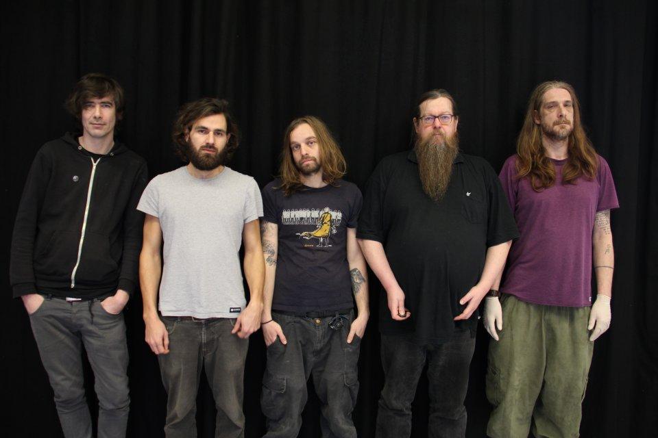 5 Männer stehen vor einem schwarzen Vorhang und schauen ernst.