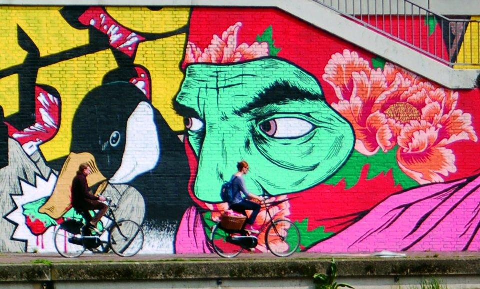 Fahrradfahrer vor riesiger Sprühlack-Zeichnung