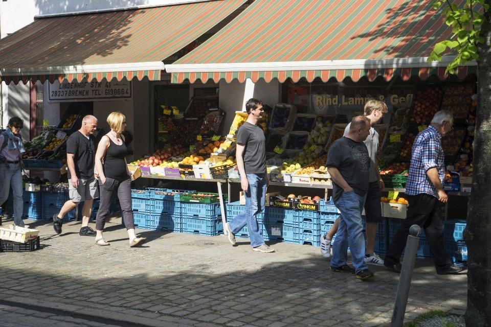 Menschen schlendern vor einem Lebensmittelgeschäft in der Lindenhofstraße. In der Auslage sind viele Obst- und Gemüsesorten zu sehen. (Quelle: Kultur vor Ort e.V.)