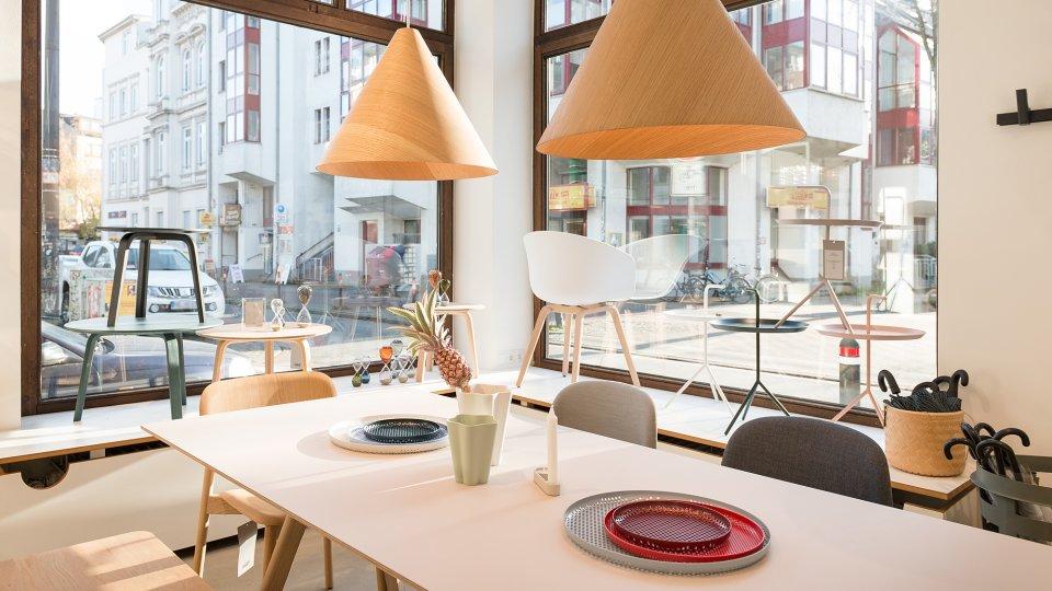 Ein Küchentisch mit Dekoartikeln im Geschäft mit Ausblick auf die Straße durch die Fenster.