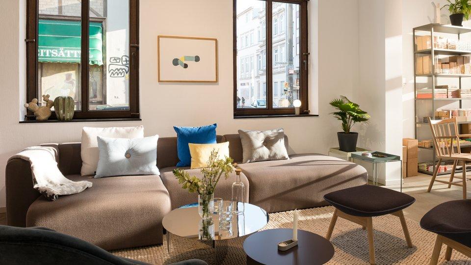 Ein Wohnzimmer im Geschäft mit Glastisch und Dekoration