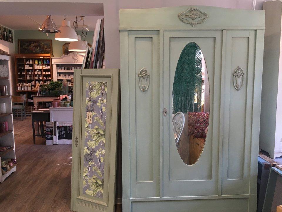 Zu sehen ist ein Schrank im Vintage Stil und ein Ausschnitt des Ladens.