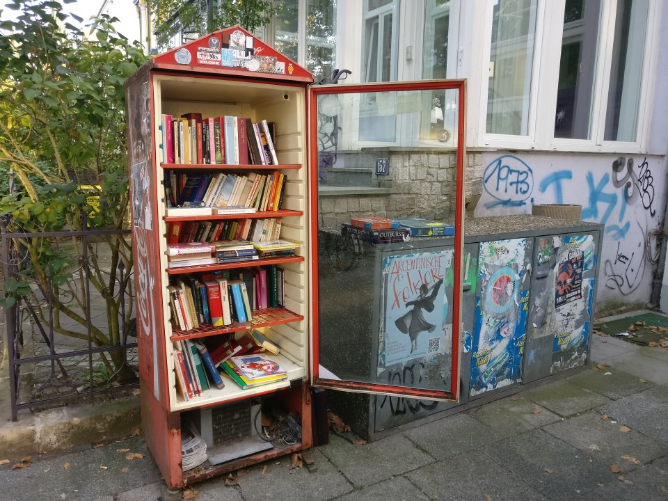 Ein alter roter Getränkekühlschrank mit Coca-Cola Aufschrift steht auf einem Gehweg. Er wurde als öffentlicher Bücherschrank umfunktioniert, in dem Schrank befinden sich Bücher.