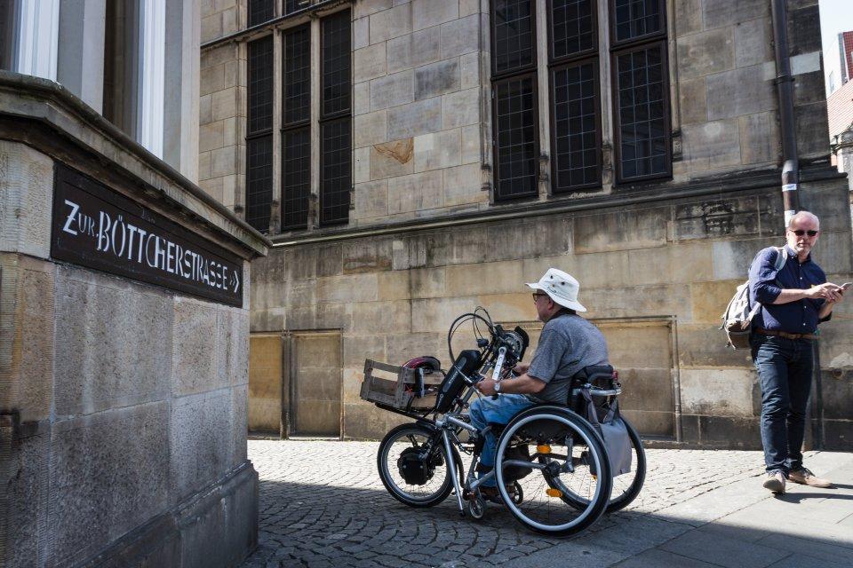 """Zwei Männer, einer mit, einer ohne Rollstuhl, links ein Schild mit Aufschrift """"Zur Böttcherstraße"""". (Foto: Nils Protze)"""