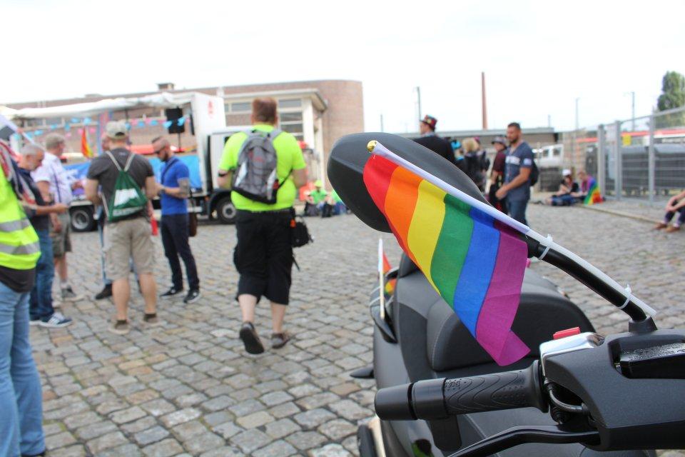 Eine Regenbogenflagge an einem Motorrad.