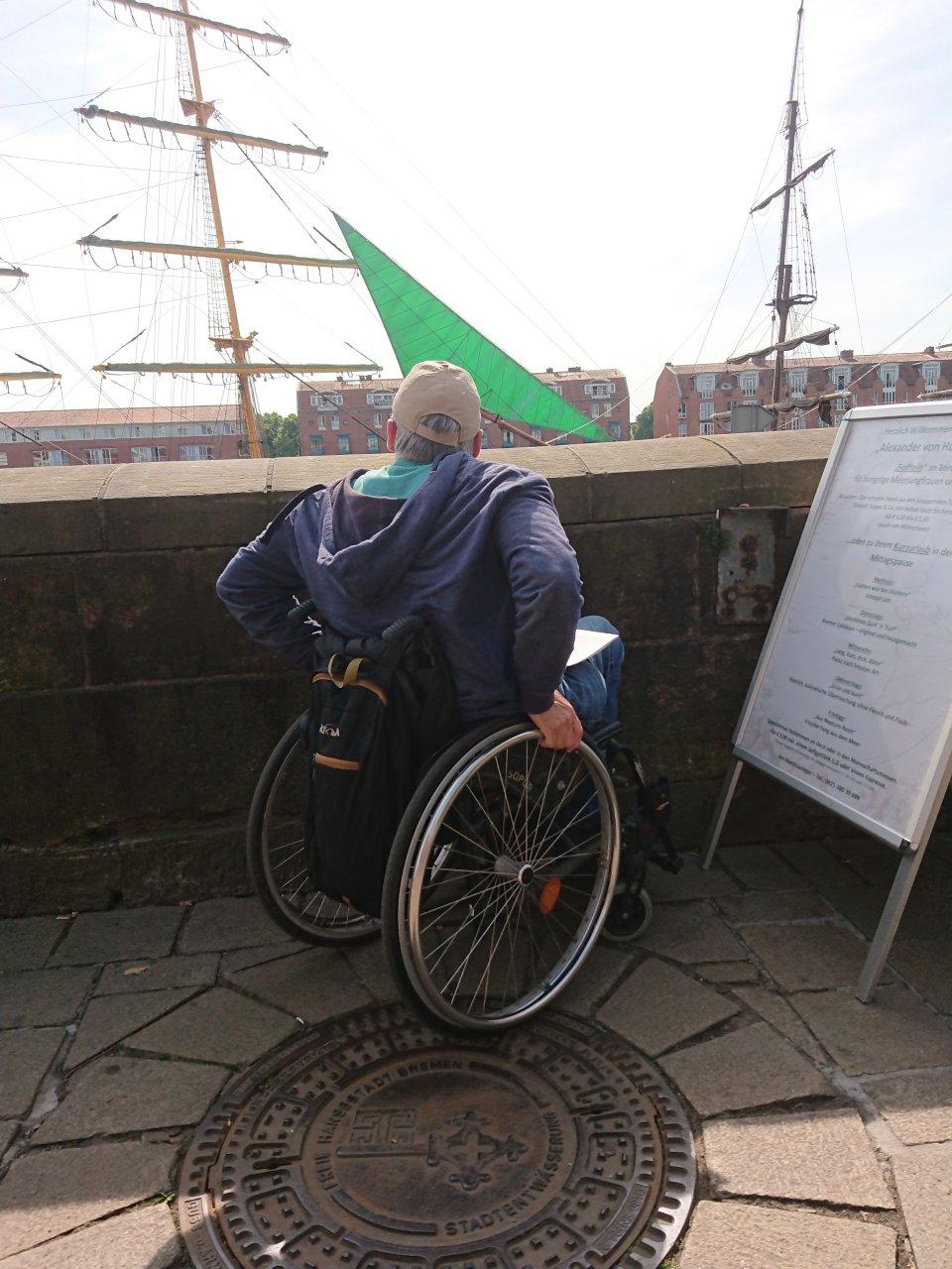 Ein Mann im Rollstuhl blickt über eine Mauer auf die Weser (Foto: Melanie Schaumburg).