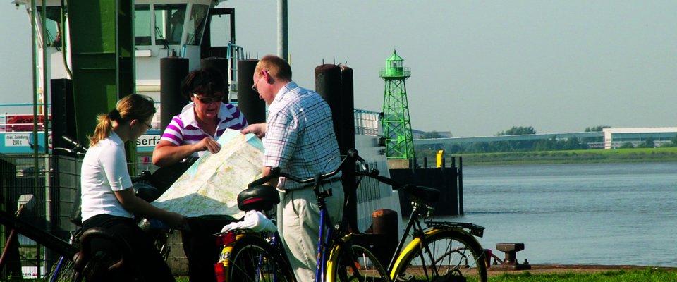 Zwei Frauen und eine Mann mit Rädern schauen auf eine Landkarte
