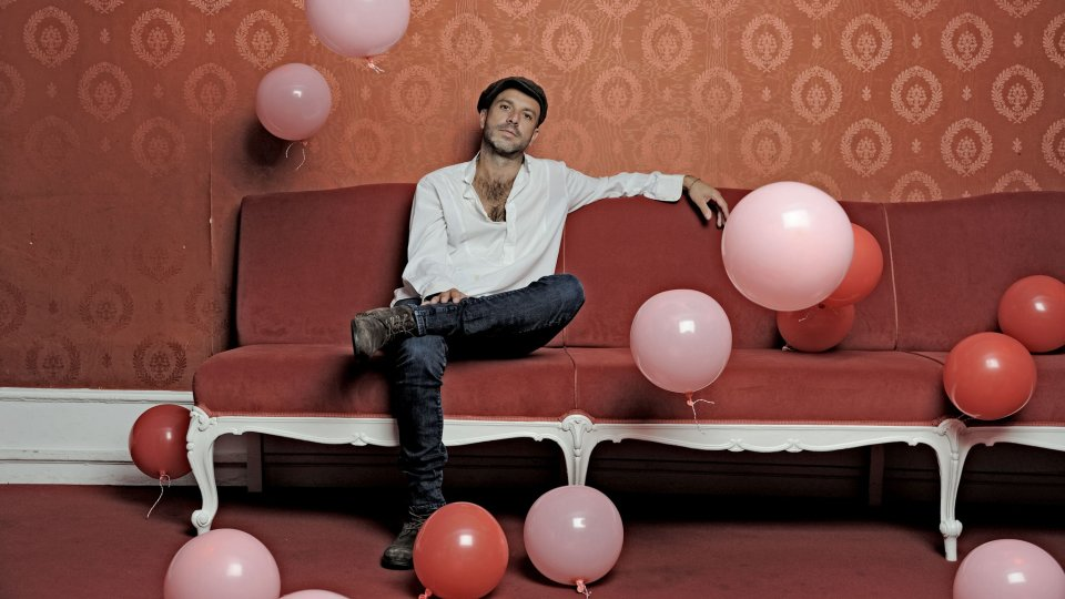Jan Plewka sitzt auf einem Sofa und um ihn herum sind Luftballons.
