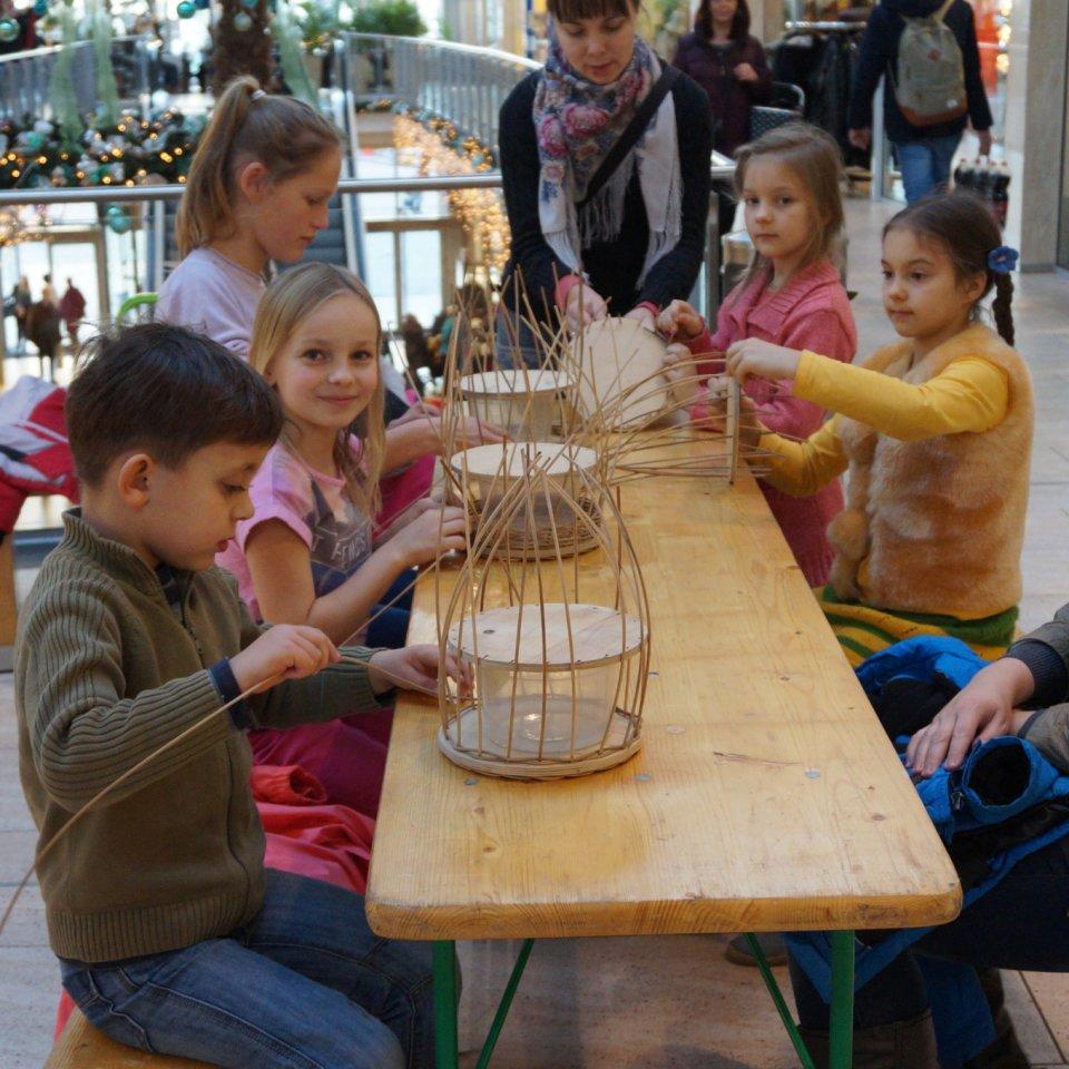 Kinder sitzen an einem Tisch mit Bänken und flechten Körbe.