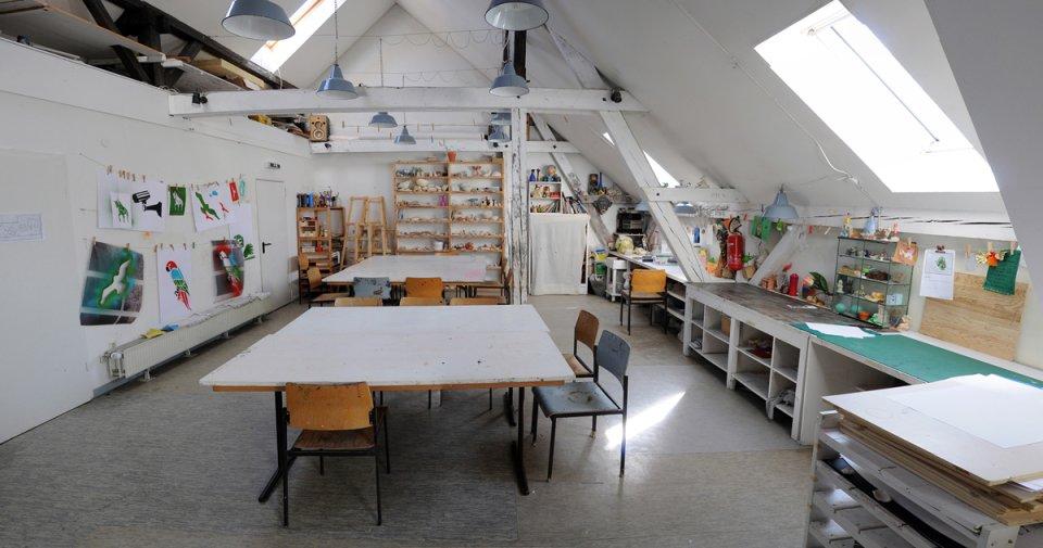 Ein Blick in das Atelier des KUBO: In dem Raum befinden sich viele Bastel- und Malutensilien, große Tische, Regale und Arbeitsflächen.